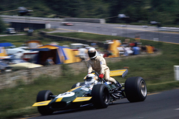 Jackie Stewart hitches a ride on the back of Derek Bell's Brabham BT26 Ford.