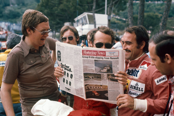 Monte Carlo, Monaco. 28-30 May 1976. Journalist Alan Henry with Ferrari drivers Niki Lauda and Clay Regazzoni and a copy of Motoring News. Ref: 76MON19. World Copyright: LAT Photographic