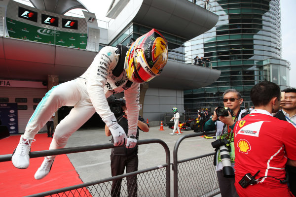 Shanghai International Circuit, Shanghai, China.  Saturday 08 April 2017.  Lewis Hamilton, Mercedes AMG, scales a fence in parc ferme after taking pole position. World Copyright: Charles Coates/LAT Images  ref: Digital Image AN7T8986