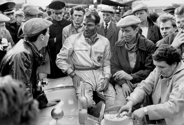Dundrod, Northern Ireland. 17th September 1955.Stirling Moss / John Fitch (Mercedes-Benz 300SLR), 1st position, chat to photo-journalist, Bernard Cahier, whilst Moss's mother cuts his 26th birthday cake, portrait.World Copyright: LAT Photographic.Ref: Autocar Glass Plate C44697.