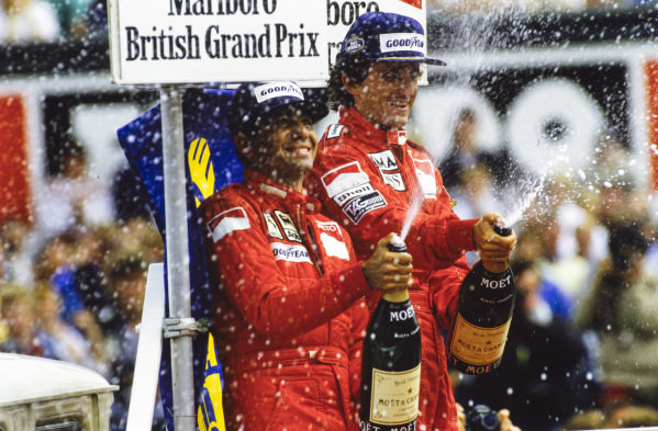 Alain Prost, 1st position, and Michele Alboreto, 2nd position, spray champagne on the podium.