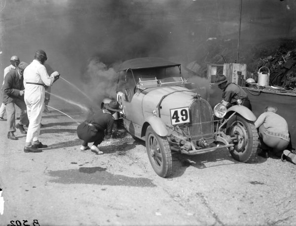 Attempts are made to extinguish Malcolm Campbell's Bugatti T43 after it caught fire in the pits.