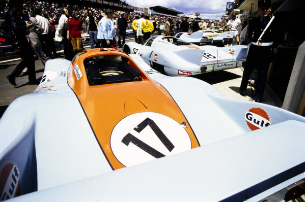 The John Wyer Automotive Engineering Porsche 917 LH's of Jo Siffert and Derek Bell (#17), Pedro Rodriguez and Jackie Oliver (#18), and Richard Attwood and Herbert Müller, lined up in the pits.