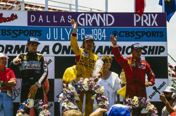 Keke Rosberg, 1st position, René Arnoux, 2nd position, and Elio de Angelis, 3rd position, celebrate on the podium. Actress Linda Gray, who played Sue Ellen Ewing in Dallas, looks on, with Carroll Shelby.