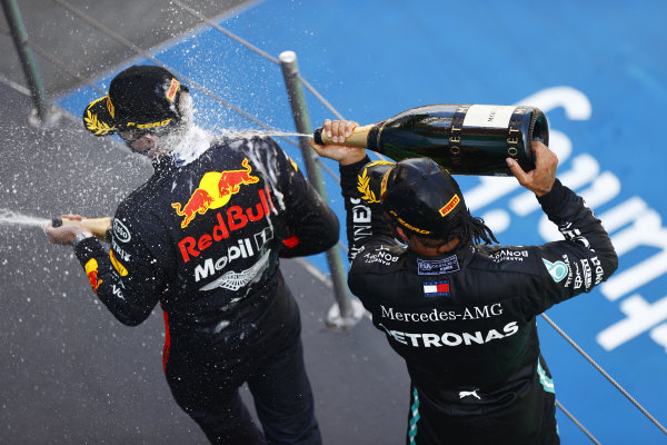 Lewis Hamilton, Mercedes-AMG Petronas F1, celebrates victory by spraying champagne over Max Verstappen, Red Bull Racing, on the podium