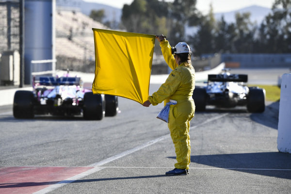 A marshal holds a yellow flag as Sergio Perez, Racing Point RP20, exits the pit lane