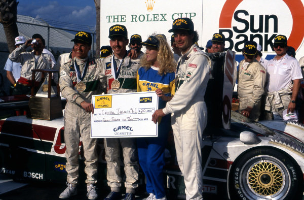 Race winners (L to R): Jan Lammers (NED) / Andy Wallace (GBR) / Davy Jones (USA), Jaguar XJR-12 (Car #61, chassis #388), celebrate with a cheque for $20,000 in victory lane. IMSA, Rd1, Daytona 24 Hours, Florida, USA. 3-4 February 1990.