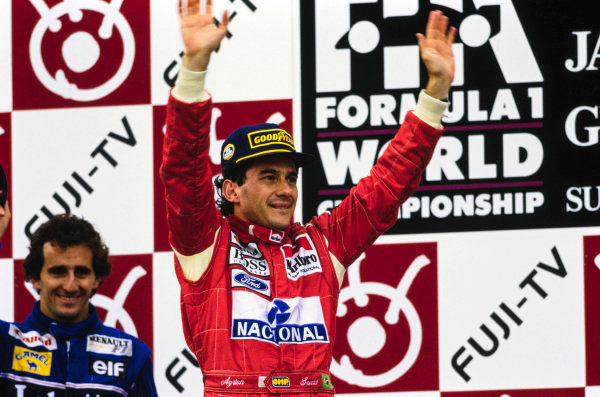 Ayrton Senna celebrates with Alain Prost on the podium.