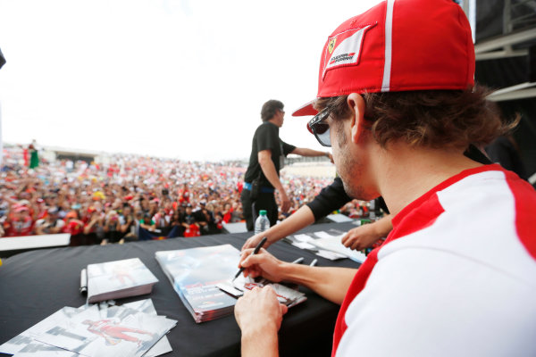 Circuit of the Americas, Austin, Texas, United States of America. Saturday 16th November 2013.  Fernando Alonso, Ferrari, signs an autograph for a fan. World Copyright: Charles Coates/LAT Photographic. ref: Digital Image _N7T9619