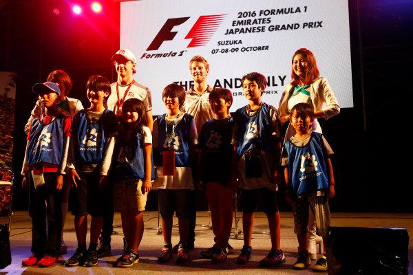 Suzuka Circuit, Japan. Saturday 08 October 2016. Esteban Gutierrez, Haas F1, Romain Grosjean, Haas F1, and children at a fan event. World Copyright: Andy Hone/LAT Photographic ref: Digital Image _ONZ4823
