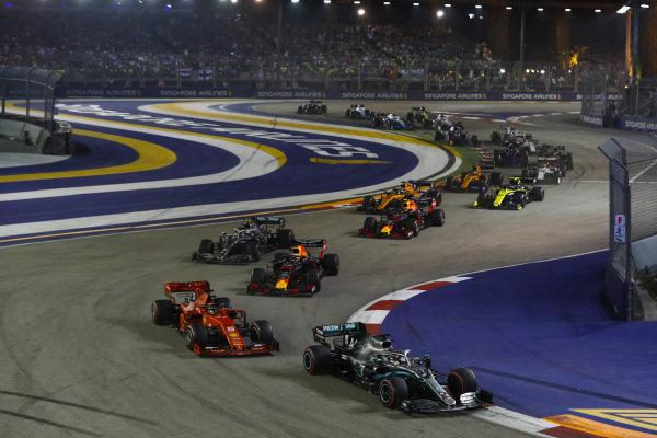Lewis Hamilton, Mercedes AMG F1 W10, leads Sebastian Vettel, Ferrari SF90, Max Verstappen, Red Bull Racing RB15, Valtteri Bottas, Mercedes AMG W10, Alexander Albon, Red Bull RB15, Carlos Sainz Jr., McLaren MCL34, and the remainder of the field at the start