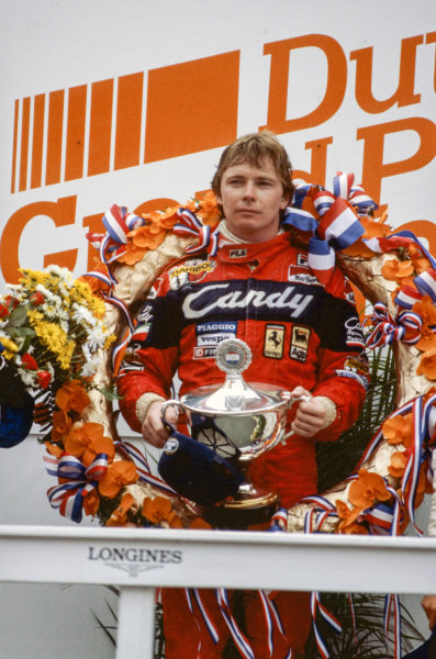 Didier Pironi, 1st position, holds his trophy on the podium.
