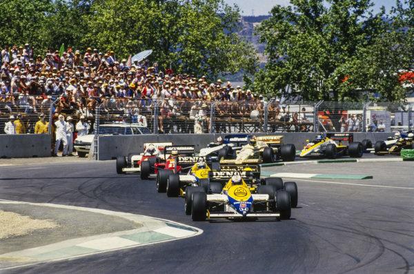 Nigel Mansell, Williams FW10 Honda, leads Ayrton Senna, Lotus 97T Renault, Keke Rosberg, Williams FW10 Honda, and Michele Alboreto, Ferrari 156/85, at the start.