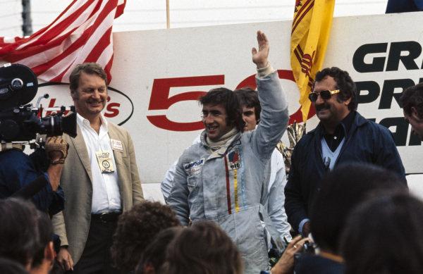 Jackie Stewart celebrates victory on the podium.