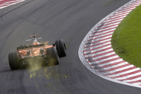Adrian Sutil's Spyker F8-VIIB Ferrari scrapes its wooden floor across the track, leaving a mark and cloud of dust in its wake.