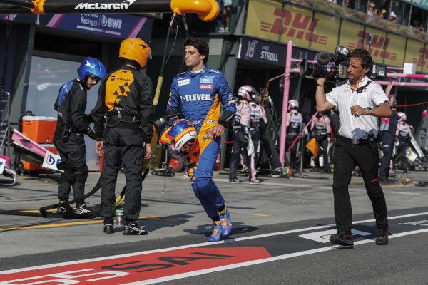 Carlos Sainz Jr, McLaren, heads back to his garage on foot after retiring at the pit lane entrance