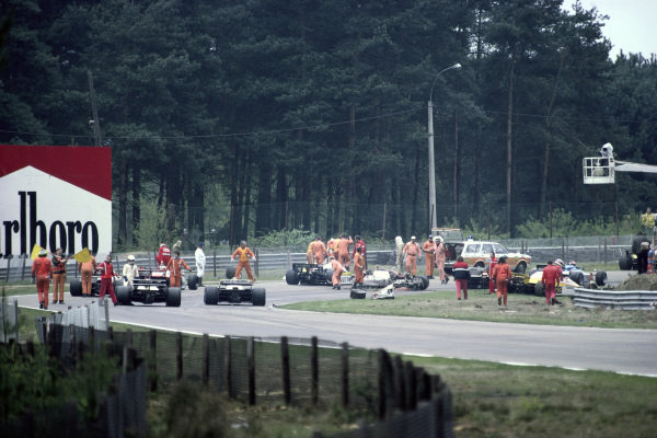 Marshals direct cars through the scene of Gilles Villeneuve's fatal accident.