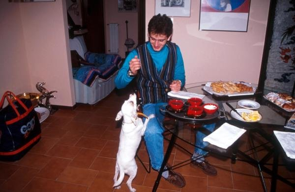 Jarno Trulli (ITA) at home teasing his pet dog as dinner is about to be served. Drivers at Home Feature, 1995, Italy.