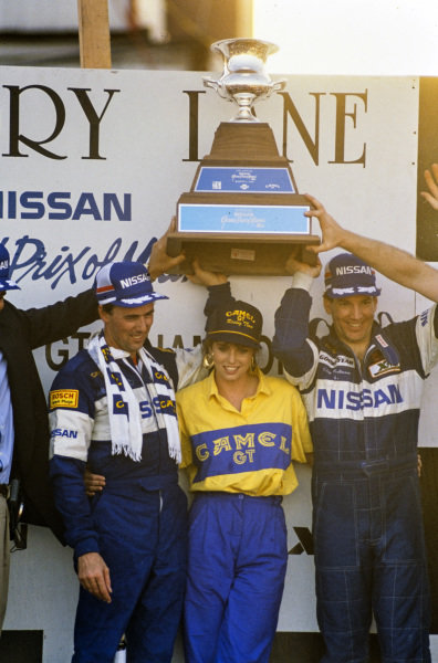 Geoff Brabham and Chip Robinson celebrate victory on the podium.