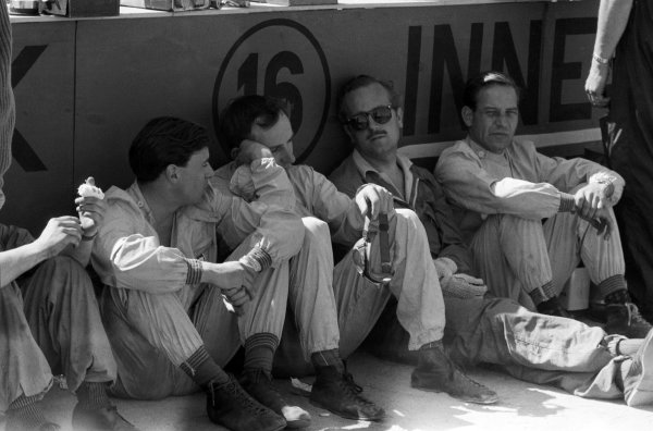 Team Lotus (L to R): Jim Clark (GBR), John Surtees (GBR), Colin Chapman (GBR) Lotus Team Owner and Innes Ireland (GBR) shelter from the heat. Portuguese Grand Prix, Oporto, Portugal, 14 August 1960.
