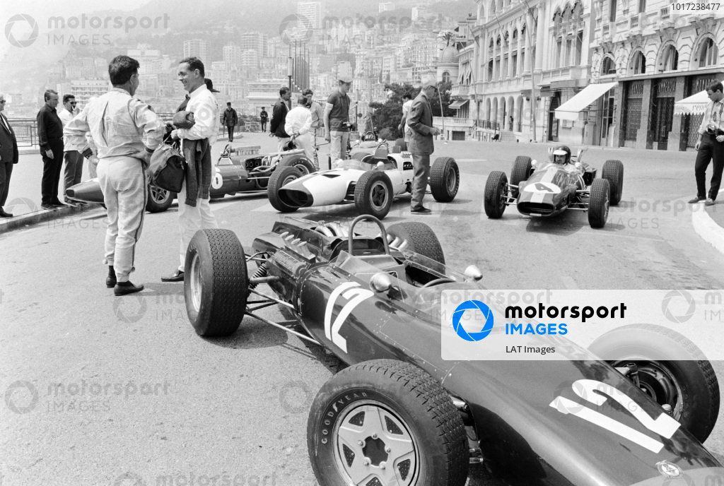 Phil Hill talks to a colleague working on the John Frankenheimer film Grand Prix. Mock-up cars are assembled, representing Jackie Stewart's BRM P261, with Bruce McLaren's McLaren M2B Ford, and Jim Clark's Lotus 33 Climax, behind.
