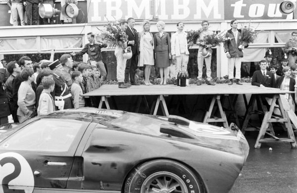 Bruce McLaren and Chris Amon, 1st position, flank Henry Ford II, his wife Maria, Colin Davis and Jo Siffert, 1st position P2.0 class, on the podium.