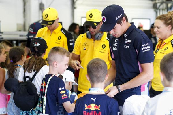 Lance Stroll, Racing Point, Daniel Ricciardo, Renault F1 Team and Nico Hulkenberg, Renault F1 Team sign autographs for Grid Kids