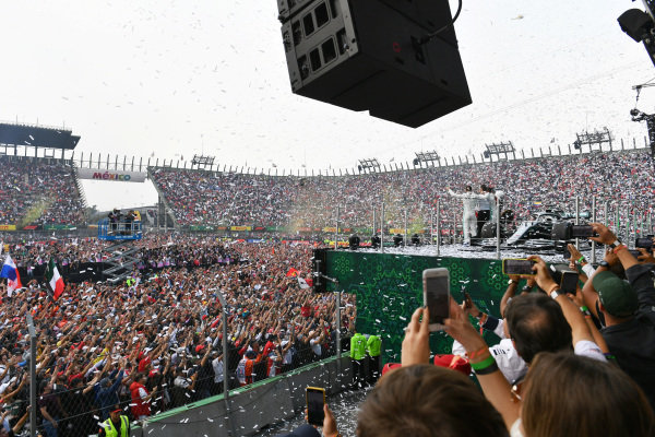 Confetti falls and the huge crowd swells as Lewis Hamilton, Mercedes AMG F1, 1st position, Sebastian Vettel, Ferrari, 2nd position, and Valtteri Bottas, Mercedes AMG F1, 3rd position, celebrate on the podium