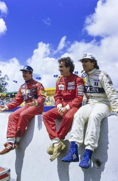 Nigel Mansell jokes alongside Alain Prost and Nelson Piquet.
