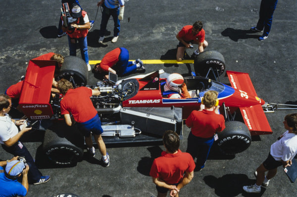 Alan Jones, Lola THL-1 Hart, in the pits as a mechanic works on the car.