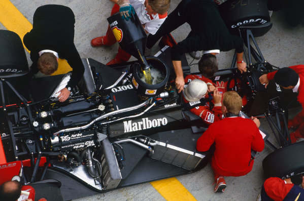Hungaroring, Budapest, Hungary. 7-9 August 1987. Alain Prost sits in his McLaren MP4/3 TAG Porsche while a mechanic adds fuel. Ref: 87HUN09. World Copyright - LAT Photographic