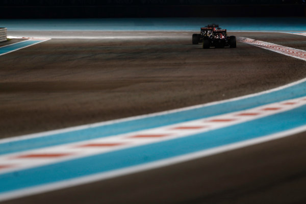Yas Marina Circuit, Abu Dhabi, United Arab Emirates. Sunday 29 November 2015. Romain Grosjean, Lotus E23 Mercedes, leads Carlos Sainz Jr, Toro Rosso STR10 Renault. World Copyright: Sam Bloxham/LAT Photographic ref: Digital Image _SBL9378