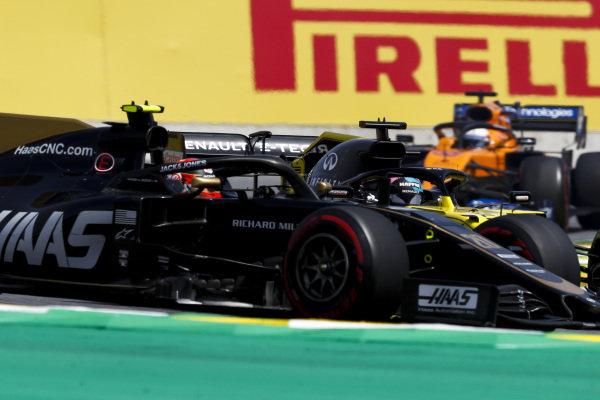 Kevin Magnussen, Haas VF-19, leads Daniel Ricciardo, Renault R.S.19, and Carlos Sainz Jr., McLaren MCL34