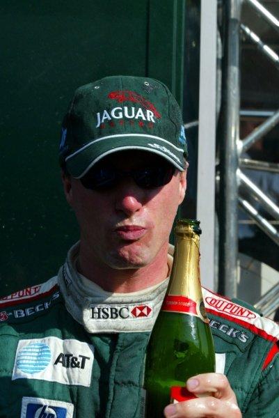 Eddie Irvine (GBR) Jaguar, celebrates his third place finish with champagne.Italian Grand Prix Race, Monza, Italy. 15 September 2002.DIGITAL IMAGE