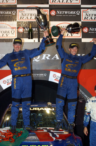2002 World Rally Championship.Network Q Rally of Great Britain, Cardiff. November 14-17. Petter Solberg (R) and Philip Mills (L) celebrate their first WRC victory on the podium.Photo: Ralph Hardwick/LAT