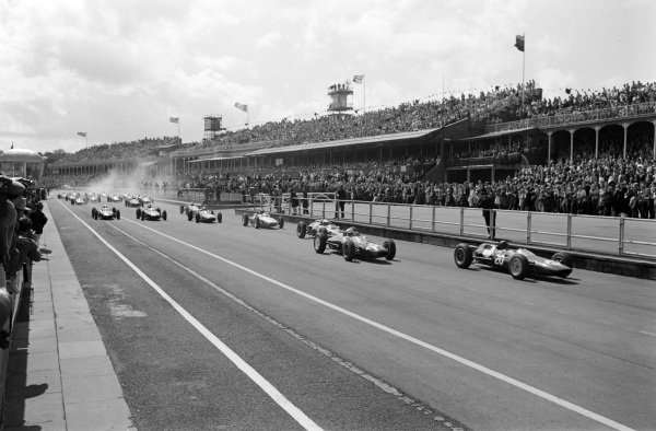 Jim Clark, Lotus 25 Climax, leads the field away at the start with John Surtees, Lola 4 Climax, and Bruce McLaren, Cooper T60 Climax, following close behind.