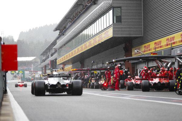 Kimi Raikkonen, Ferrari SF71H, and Sebastian Vettel, Ferrari SF71H, make pit stops for intermediate tyres, as Romain Grosjean, Haas F1 Team VF-18, passes by.