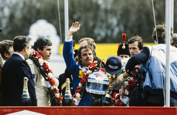 Keke Rosberg, 1st position, waves on the podium. Beside are Danny Sullivan, 2nd position, and Alan Jones, 3rd position.