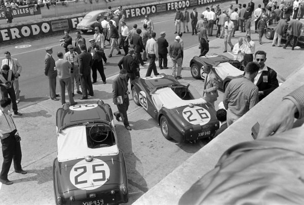 The Triumph TR3 S's of Peter Jopp / Richard Stoop (#25), Peter Bolton / Michael Rotschild (#26), and Ninian Sanderson / Claude Dubois (#27) in the pits.