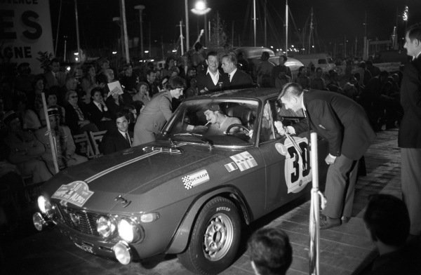Anssi Järvi recieves a light fo rhis cigarette whilst Hannu Mikkola is interviewed at the rally start.