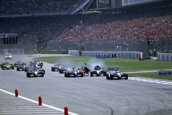 Juan Pablo Montoya, Williams FW25 BMW, leads Kimi Räikkönen, McLaren MP4-17D Mercedes, who has been wiped out of the race immediately in a collision with Rubens Barrichello, Ferrari F2003-GA, Ralf Schumacher, Williams FW25 BMW, and Jarno Trulli, Renault R23B, at the start.