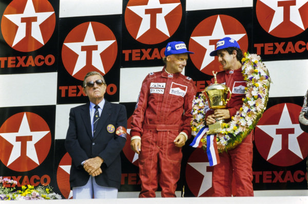 Alain Prost, 1st position, Niki Lauda, 2nd position, and FIA/FISA President Jean-Marie Balestre on the podium.