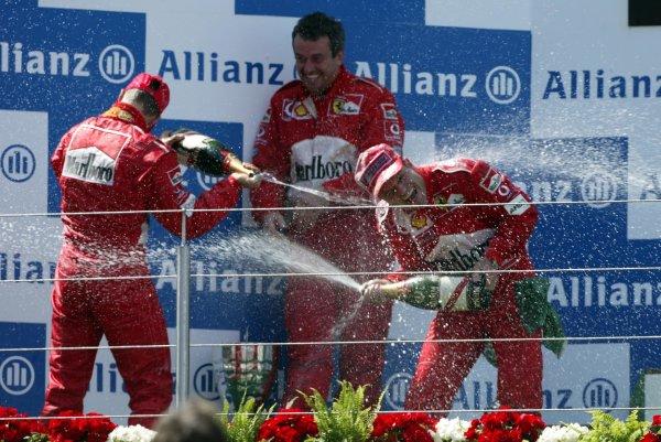 2002 European Grand Prix - RaceNurburgring, Germany. 23rd June 2002Michael Schumacher, Ferrari F2002, 2nd, and race winner Rubens Barrichello, Ferrari F2002, spray Nigel Stepney with champagne.World Copyright: Steve Etherington/LATref: Digital Image Only