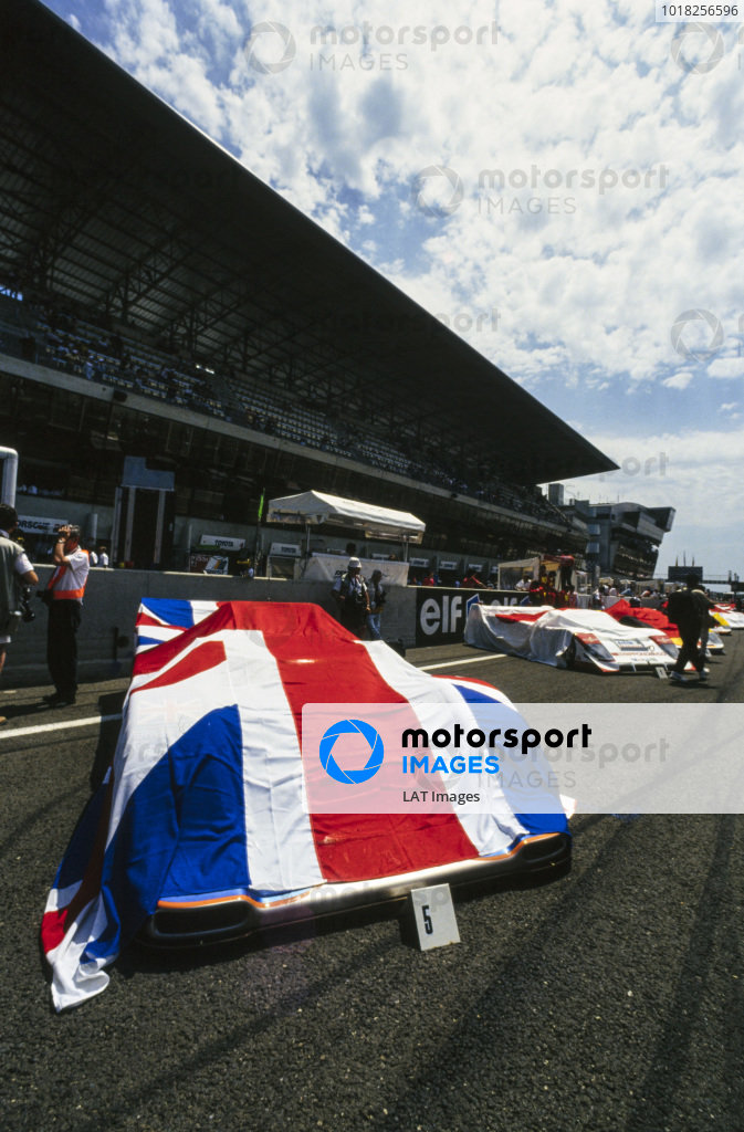 A Union flag covers Derek Bell, Robin Donovan, and Jürgen Lässig's Kremer CK8 Spyder Porsche on the grid.