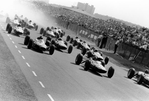 1964 Dutch Grand Prix.Zandvoort, Holland. 22-24 May 1964.Graham Hill (right, BRM P261) leads Jim Clark (#18 Lotus 25-Climax), Dan Gurney (#16 Brabham BT7-Climax), John Surtees (#2 Ferrari 158), Bruce McLaren (#24 Cooper T73-Climax), Peter Arundell (#20 Lotus 25-Climax), Jack Brabham (#14 Brabham BT7-Climax) and Richie Ginther (#8 BRM P261) at the start.World Copyright: LAT PhotographicRef: Autosport b&w print