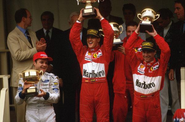Monte Carlo, Monaco.8-11 May 1997.Michael Schumacher (Ferrari) 1st position, Eddie Irvine (Ferrari) 3rd position and Rubens Barrichello (Stewart Ford) 2nd position celebrate on the podium. .Ref-97 MON 09.World Copyright - LAT Photographic