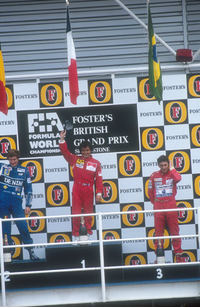 1990 British Grand Prix.Silverstone, England.13-15 July 1990.Alain Prost (Ferrari) celebrates his 1st position with Thierry Boutsen (Williams Renault) 2nd position and Ayrton Senna (McLaren Honda) 3rd position on the podium.Ref-90 GB 15.World Copyright - LAT Photographic