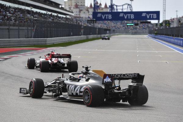 Charles Leclerc, Ferrari SF90, leads Romain Grosjean, Haas VF-19