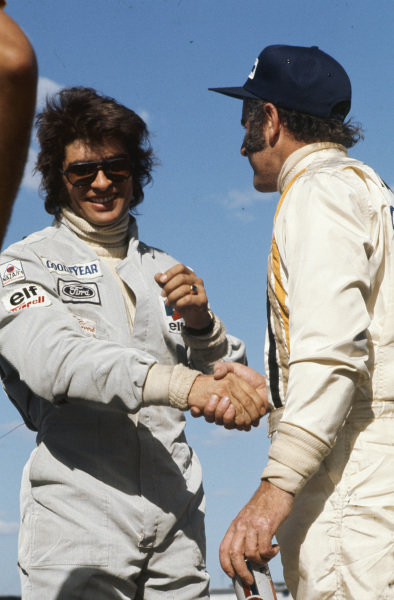 Race winner Denny Hulme is congratulated on the podium by 3rd placed François Cevert.