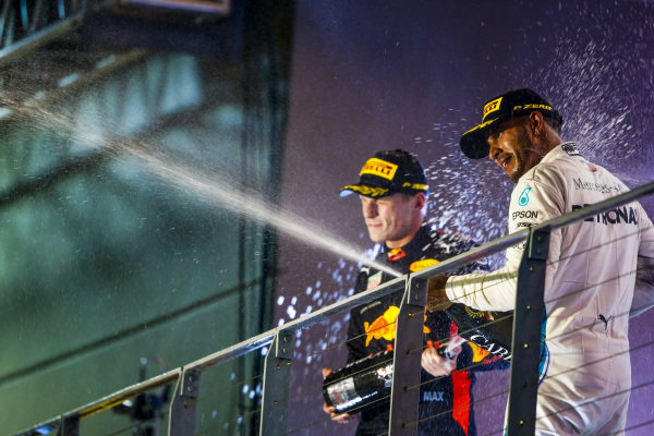 Max Verstappen, Red Bull Racing, 2nd position, and Lewis Hamilton, Mercedes AMG F1, 1st position, celebrate with Champagne on the podium